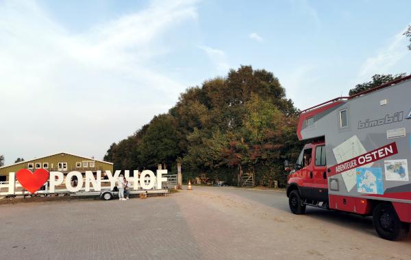 """Wohnmobil neben """"I love Ponyhof""""-Anhänger"""
