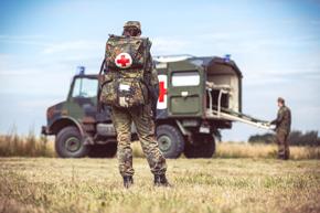 Pfleger vor Militärauto