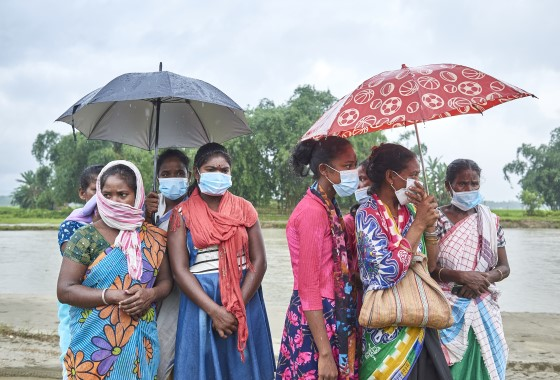 The image shows a group of women standing in front of a flooded river, photo by Indian Red Cross Society