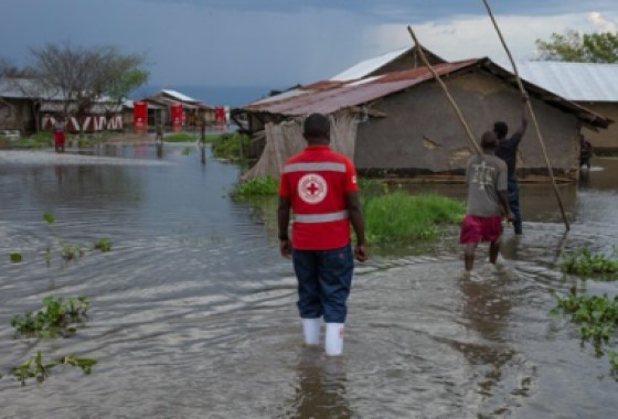 The image shows three people walking through a flooded village.