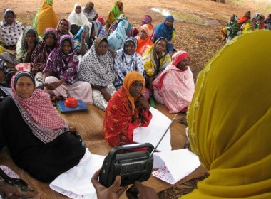 The image shows a groups of women sitting on the ground while listening to a local radio broadcast
