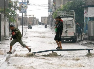 This image shows two men crossing a flooded street