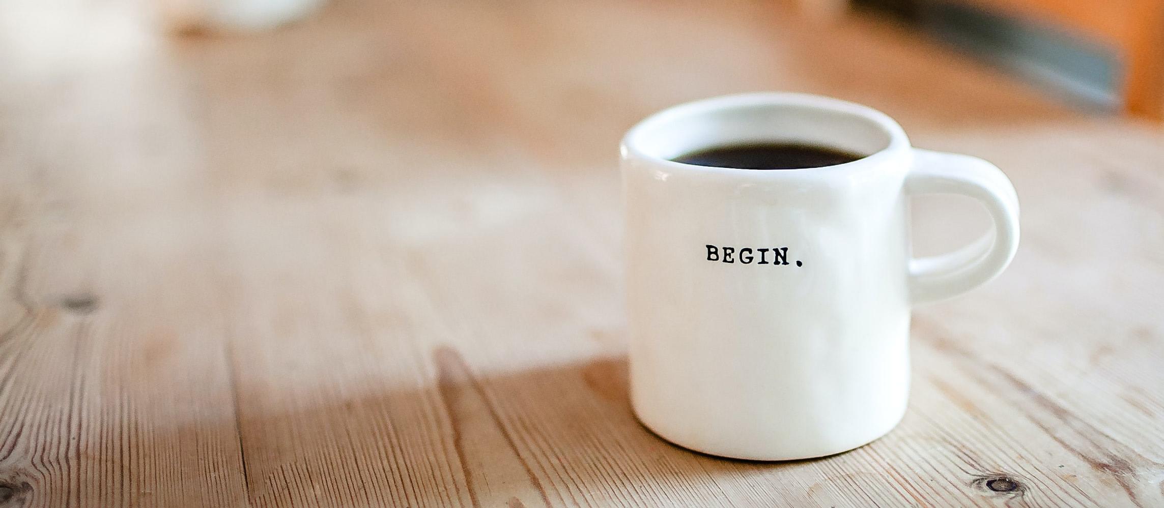 """Kaffeetasse mit Aufschrift """"Begin"""" (danielle macinnes unsplash)"""