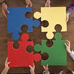 Vier Menschen halten je ein Puzzelteil aneinander, so dass ein Quadrat entsteht.