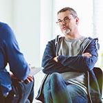 Berater und Klient sitzen sich gegenüber und sprechen miteinander.