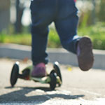 Ansicht von hinten von einem Kind, das auf einem Trottinett auf der Strasse fährt.