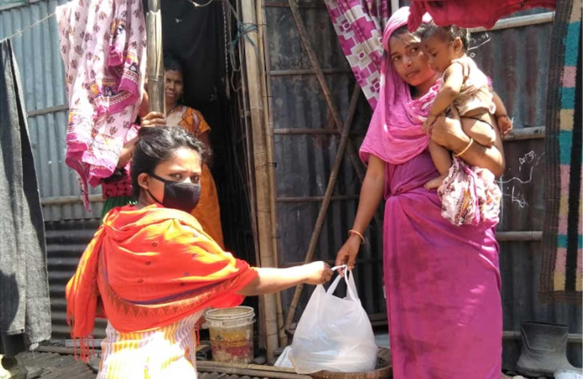 Eine ehrenamtliche Helferin verteilt Lebensmittel an eine Familie in Indien, die wegen der Coronamaßnahmen nicht mehr arbeiten kann.