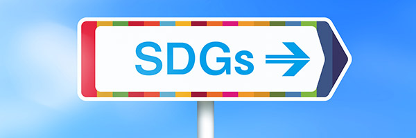 """Bild eines Schildes mit der Aufschrift """"SDGs"""" mit einem Hintergrund von frischem Grün und Wolken - Lizenzfrei Anführen Stock-Foto"""