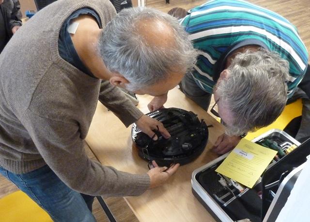 Reparateure reparieren einen Staubsauger