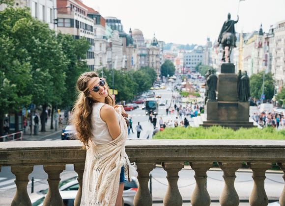 Eine junge Frau, die auf dem Wenzelplatz in Prag steht, lächelt in die Kamera