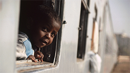 Boy looks out a train window