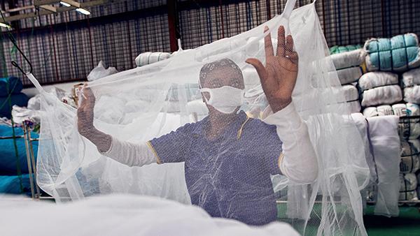 Factory worker checks mosquito nets