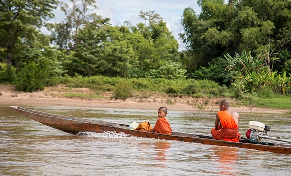 Two buddhist monks in a boat on a river