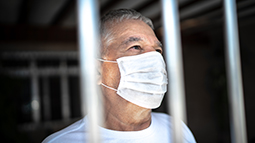 Man with face mask behind bars