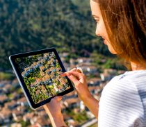 Frau mit Tablet schaut auf ein Dorf, Quelle: stock.adobe.com/rh2010