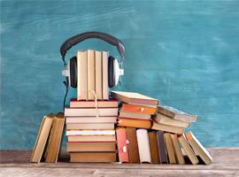 Bücherstapel mit Kopfhörer. thomas-bethge / iStock / Getty Images Plus via Getty Images