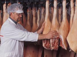 Mann neben Schweinehälften
