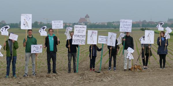 Menschen mit Schildern auf einem Acker. / Foto: Unser Land schafft Wandel